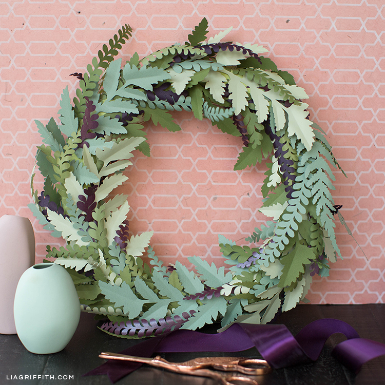 Table with scissors, small vases, ribbon, and paper fern wreath learning against patterned wall
