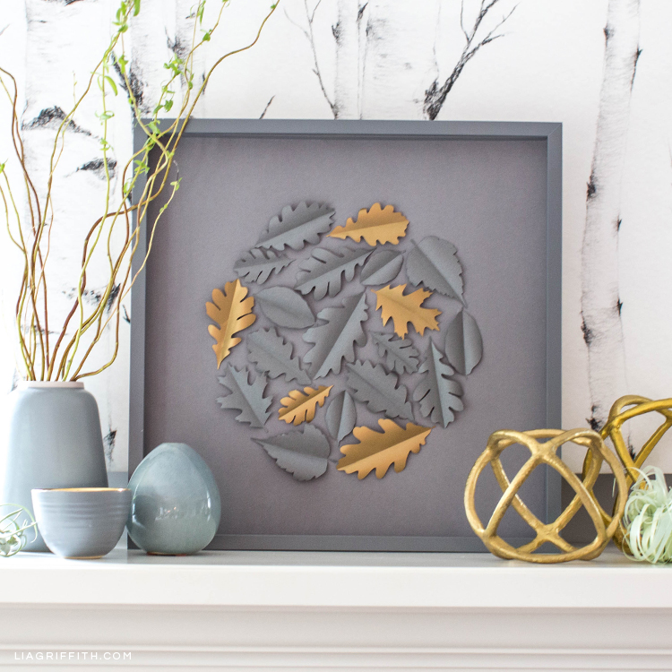 Papercut oak leaf framed art on white mantle with vases and home decor
