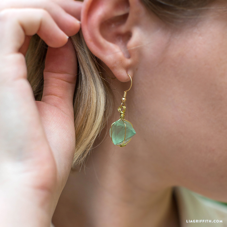 Close-up of of wire wrapped crystal earring in one ear