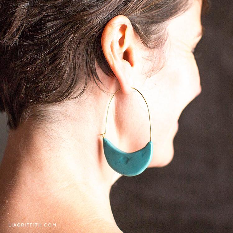 Woman wearing polymer clay crescent hoop earrings