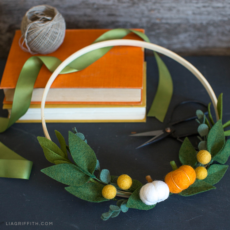 Mini pumpkin and greenery wreath next to books, ribbon, and twine