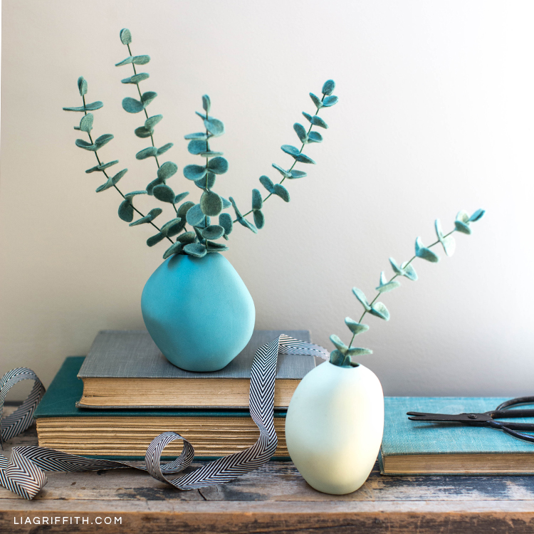 Baby blue eucalyptus plants in vases on table next to books, ribbon, and scissors