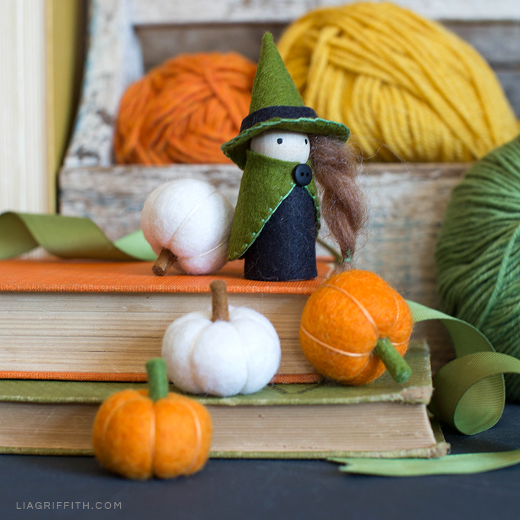 Mini felt pumpkins with DIY witch peg doll on books next to yarn