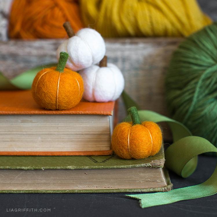 Mini felt pumpkins on books next to yarn
