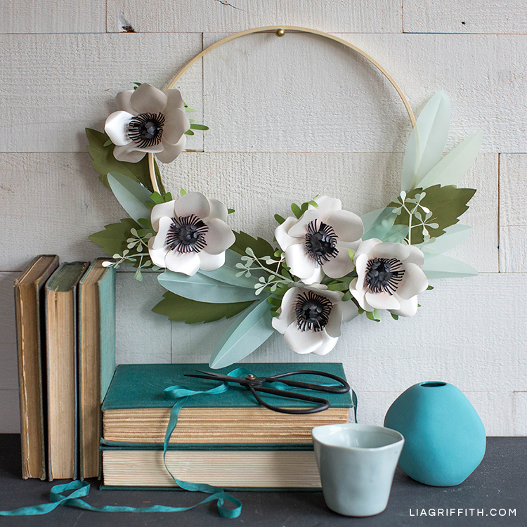 Anemone and eucalyptus wreath hanging on wall above books, scissors, and vase
