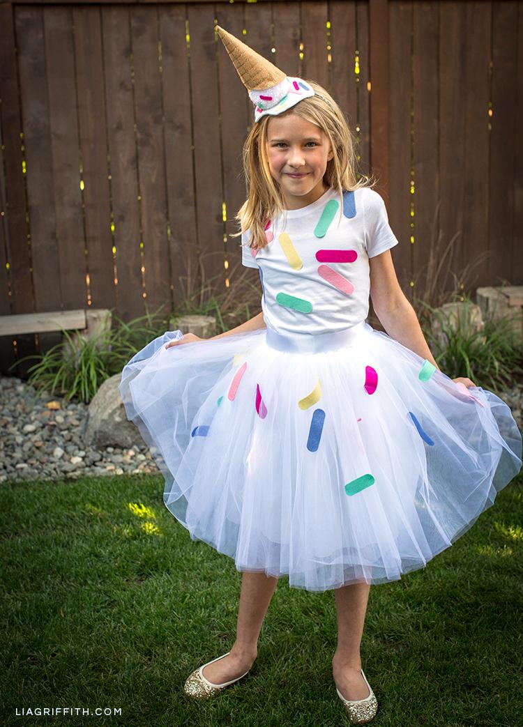 Girl wearing DIY ice cream cone costume in backyard