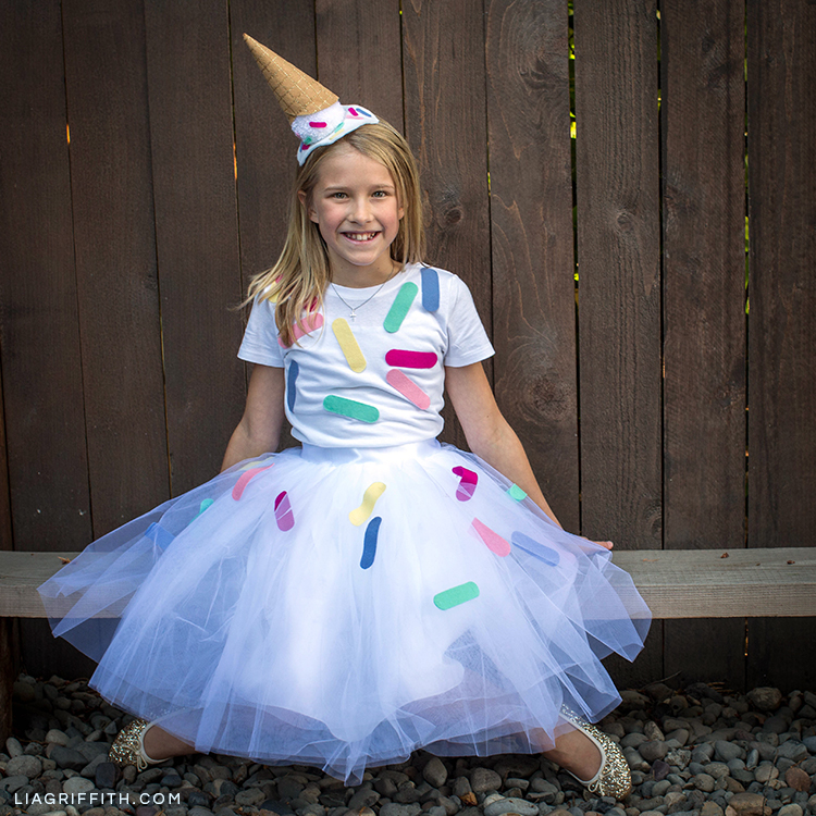 Girl wearing DIY ice cream cone costume on bench
