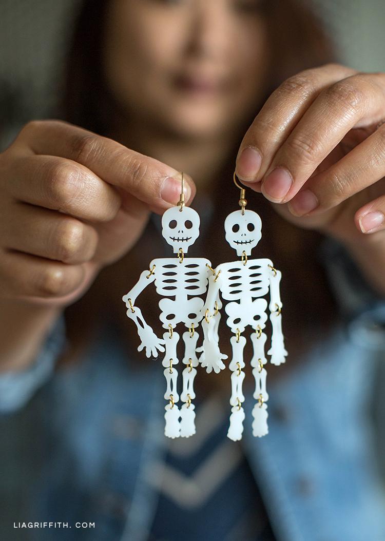 Woman holding shrink film skeleton earrings