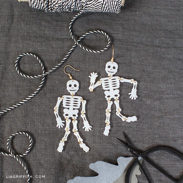 Shrink film skeleton earrings next to craft materials