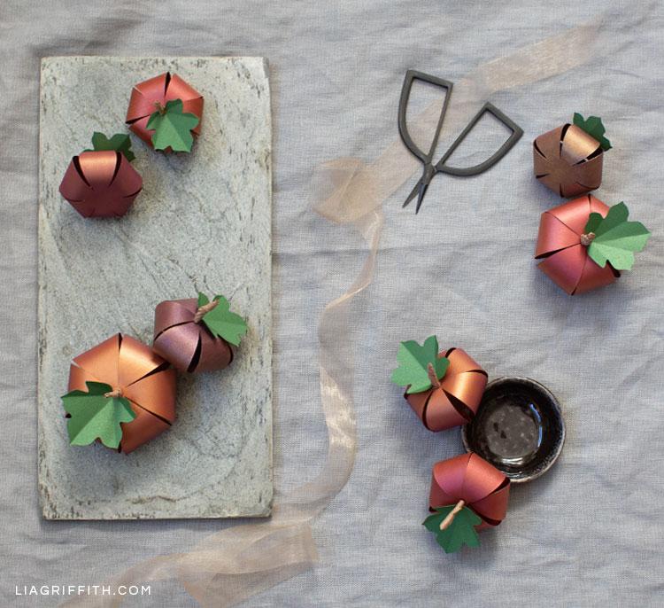 ombré paper pumpkins next to scissors and ribbon