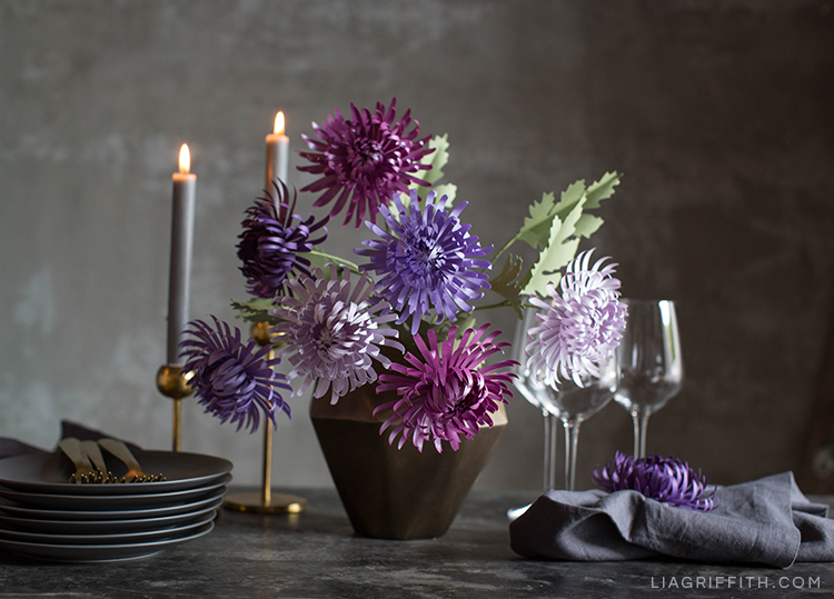 Purple paper spider chrysanthemums in vase next to plates, candles, and glasses on table