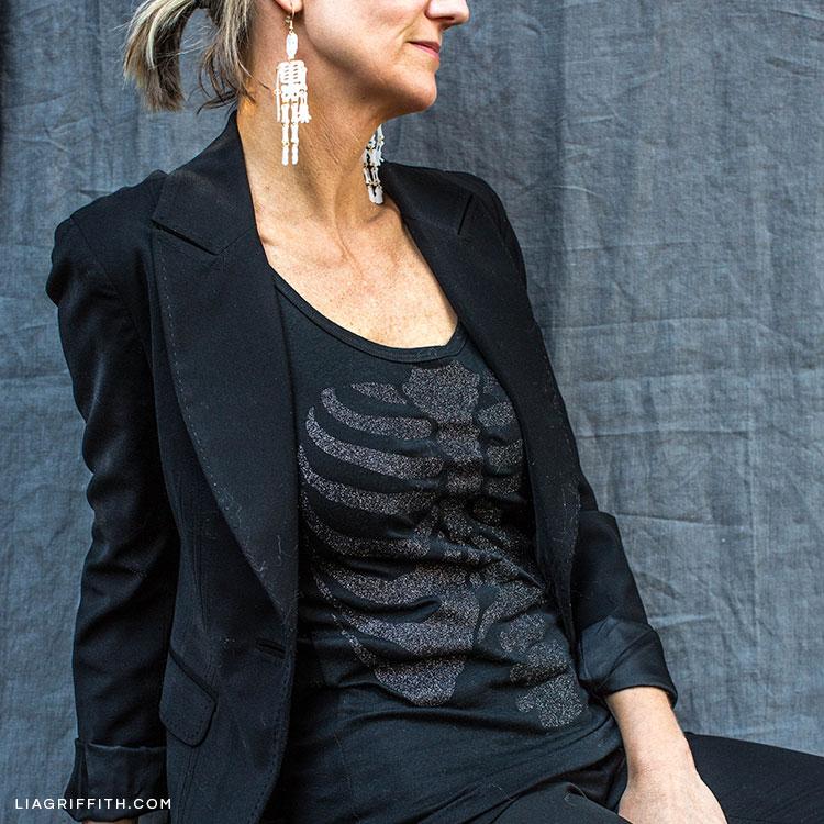 Woman wearing DIY skeleton top and DIY skeleton earrings for Halloween