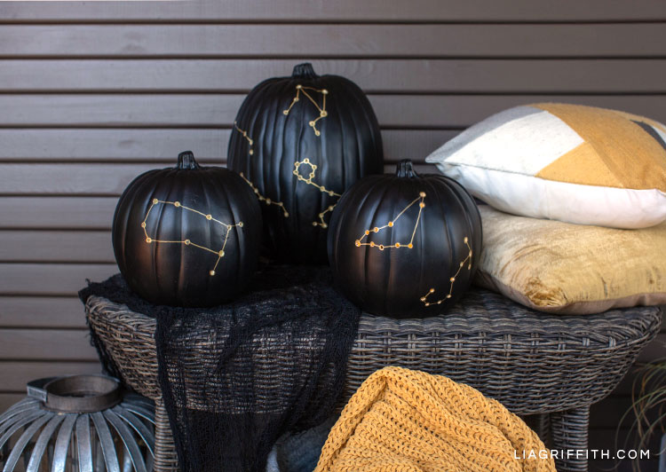 Constellation pumpkin luminaries on wicker table next to pillows