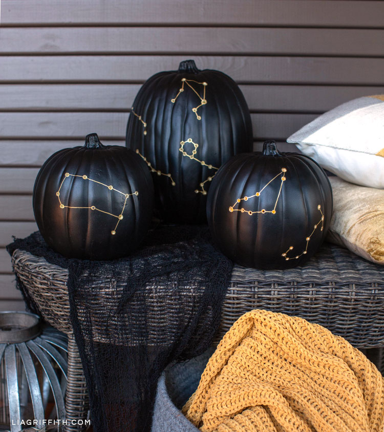 Constellation pumpkin luminaries on wicker table next to pillows and blanket