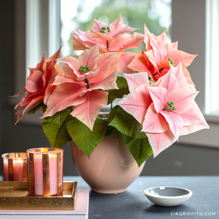 pink crepe paper poinsettia plants in vase next to candles on table
