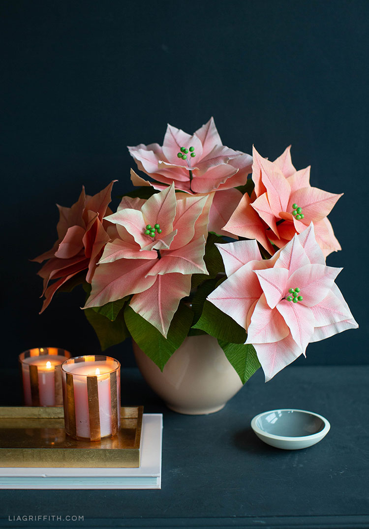 pink crepe paper poinsettia plants in vase next to candles and small dish