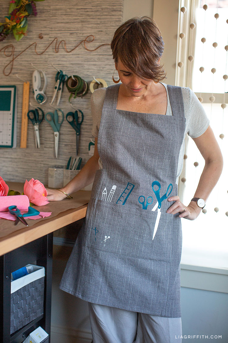 Woman wearing DIY craft apron with iron-on designs in craft room