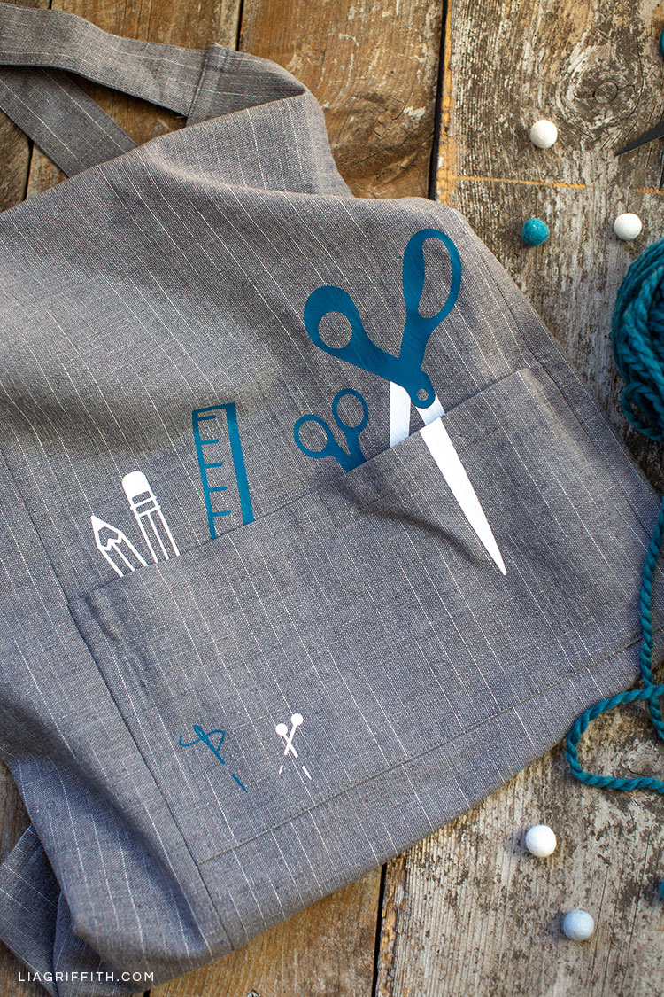 DIY craft apron with iron-on designs featuring scissors, ruler, and pencils