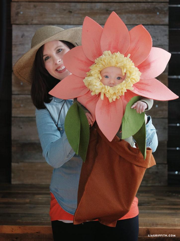 Mom in gardener costume holding baby in felt flower halloween costume