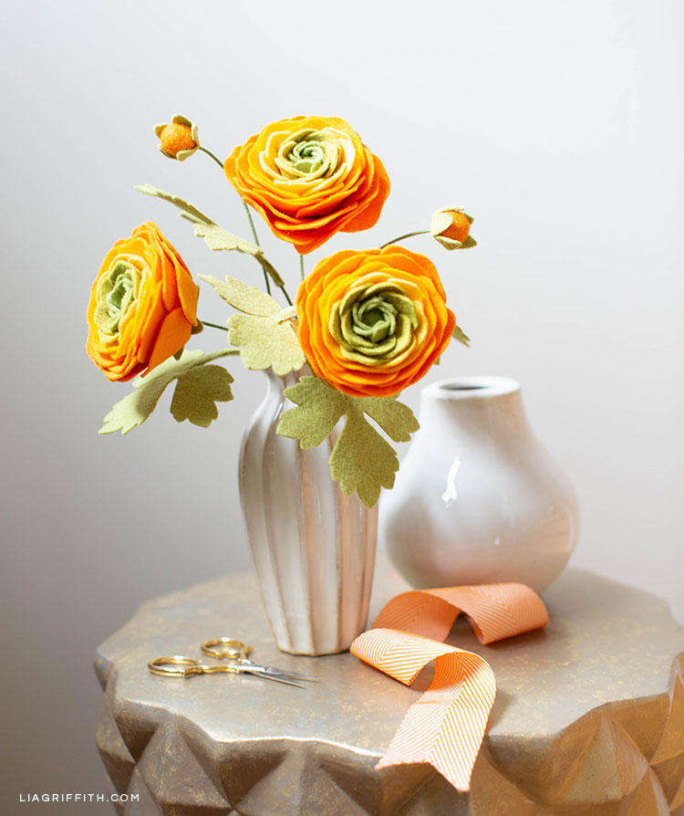Felt ranunculus flowers in vase on table next to ribbon and scissors