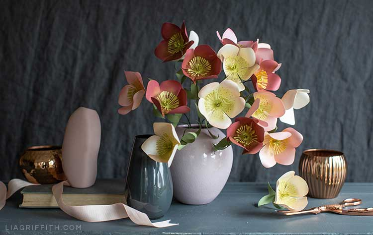 Red and pink frosted paper Hellebore flowers in pink vase next to empty vases