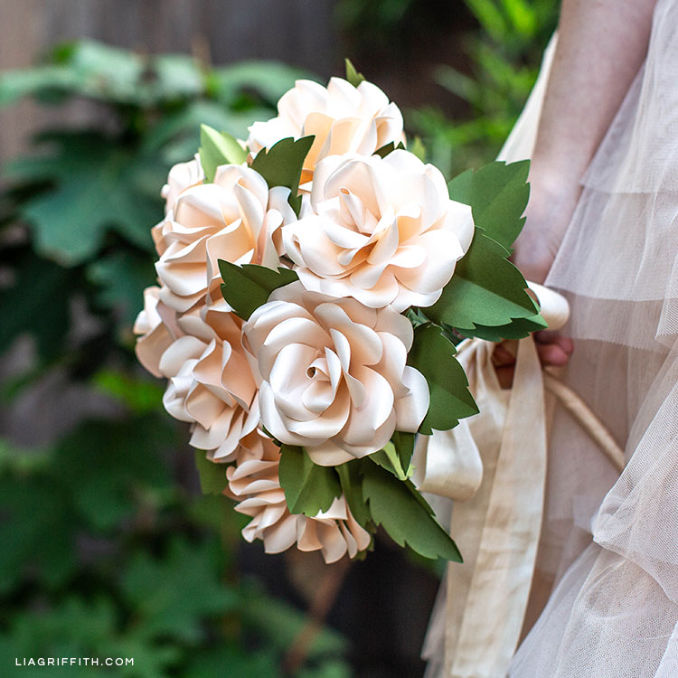 Woman holding frosted paper rose bridal bouquet outside