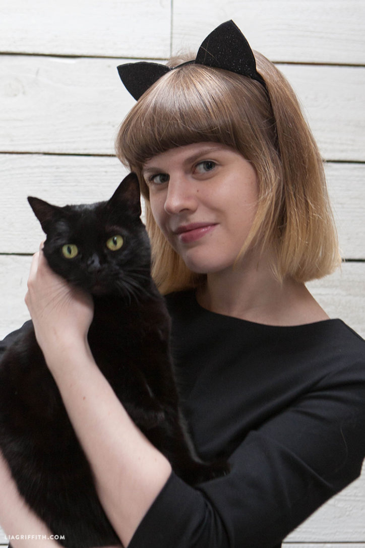 woman holding cat and wearing DIY cat ears for Halloween