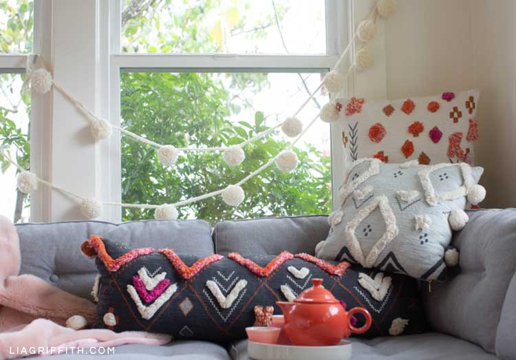 jumbo pom-pom garland hanging across window and behind couch with pillows
