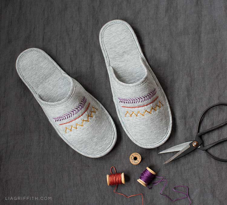 DIY embroidered slippers next to scissors and embroidery floss