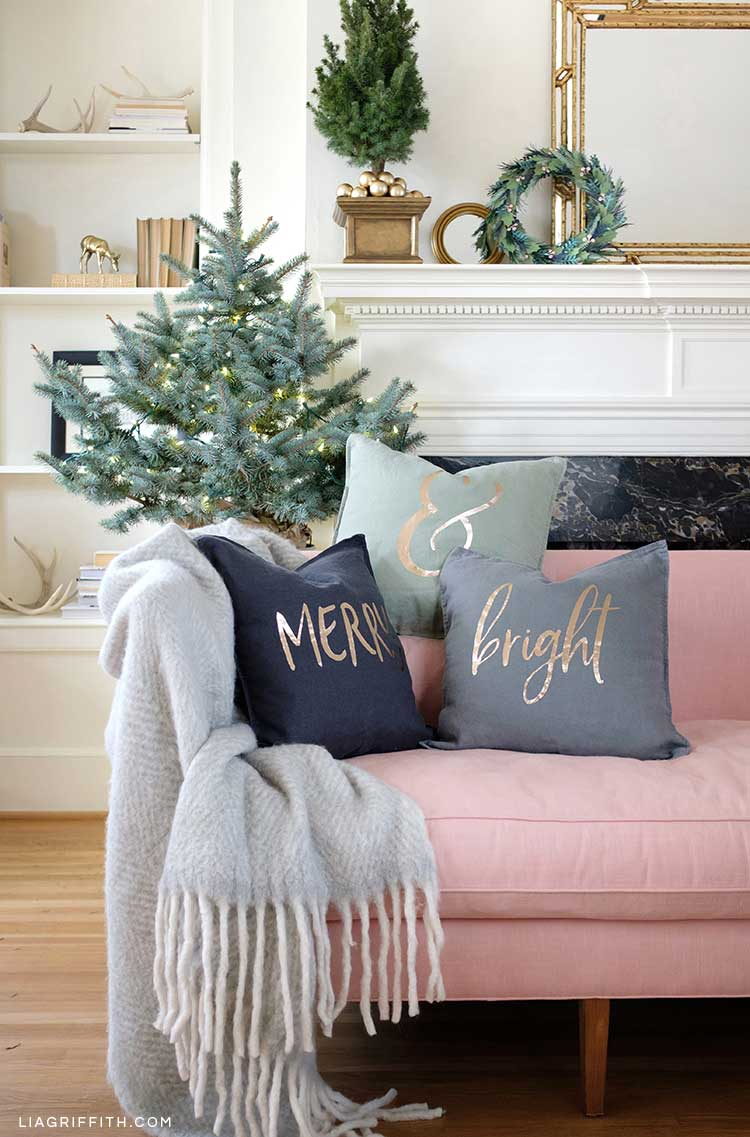 merry & bright holiday pillows on pink couch in front of Christmas tree and fireplace mantel with décor