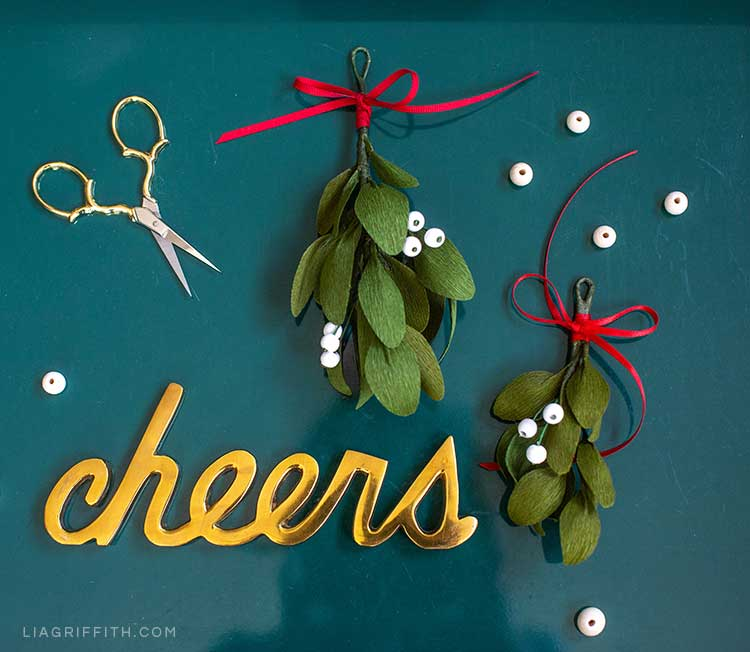 DIY crepe paper mistletoe next to gold cheers sign and scissors