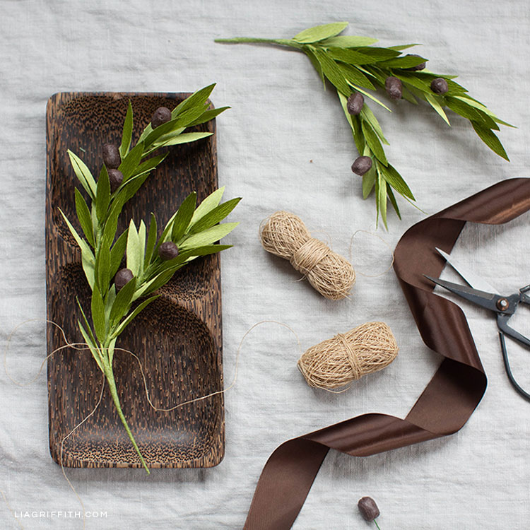 crepe paper olive branch on wooden decorative tray with brown ribbon, twine, scissors, and olive branch