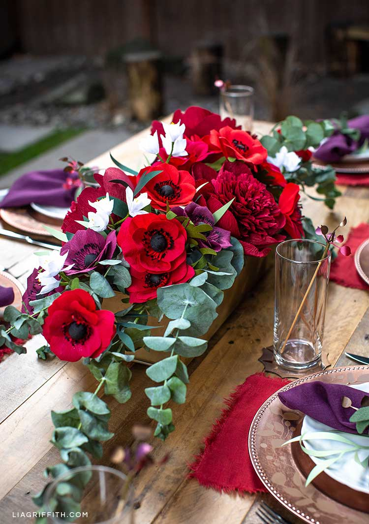 Centerpiece floral arrangement with paper flowers and plants on table