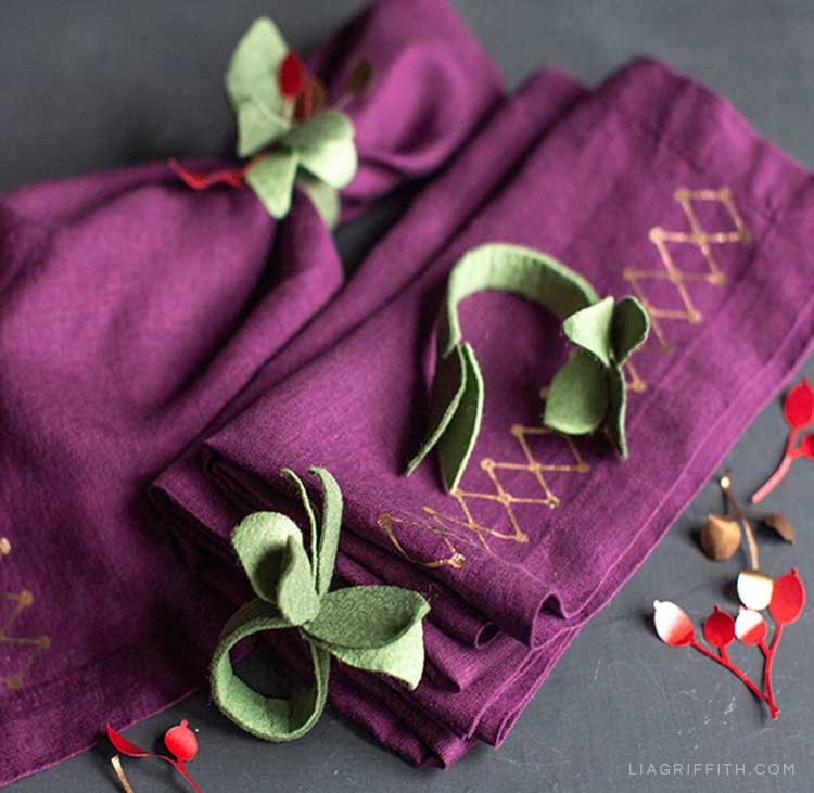 Purple linens with DIY designs and felt napkin rings with paper berries