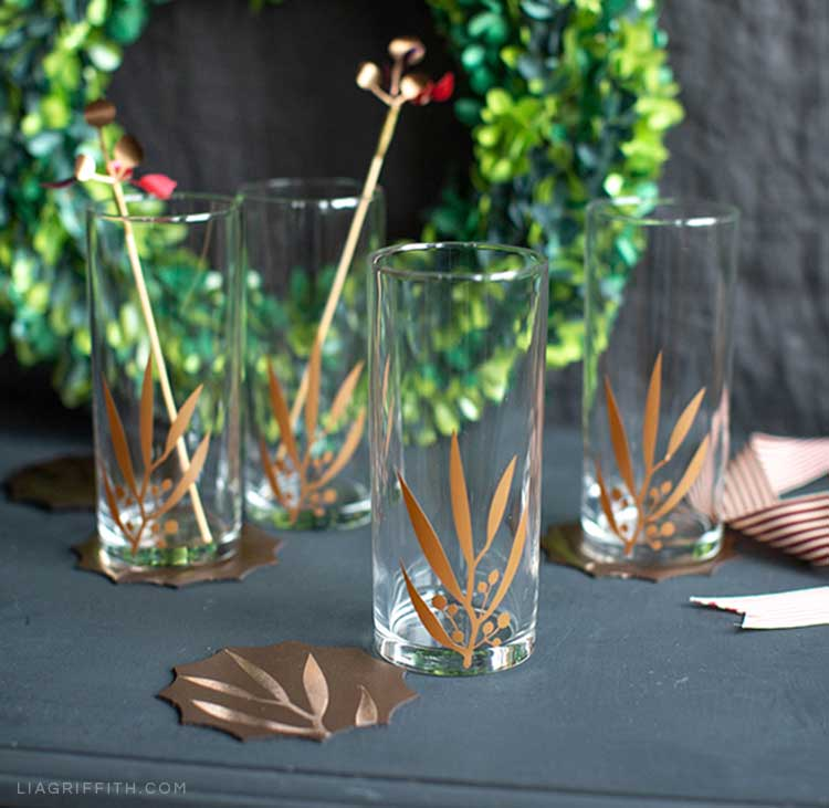 Glasses with DIY leaf designs on table in front of paper wreath