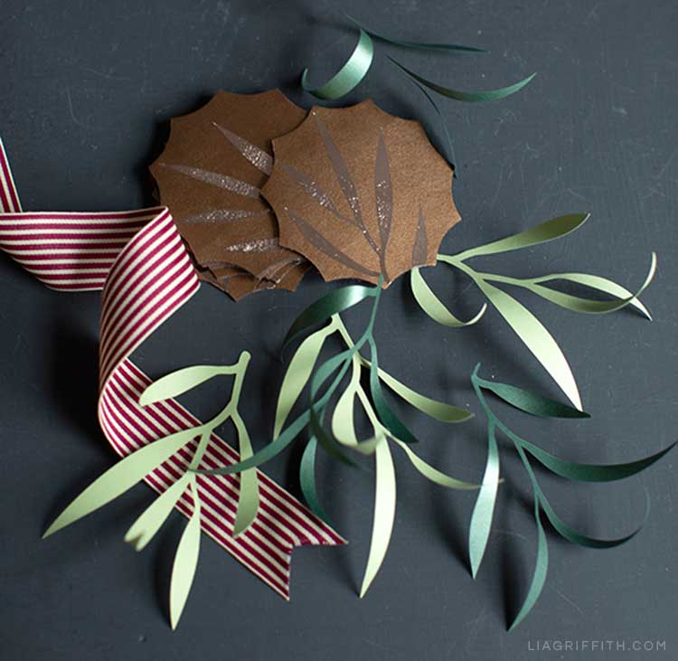 Leather coasters with DIY leaf designs, paper leaves, and ribbon