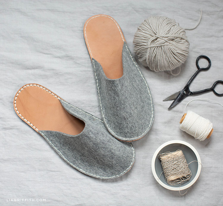 DIY felt and leather slippers next to grey yarn, thread, and scissors