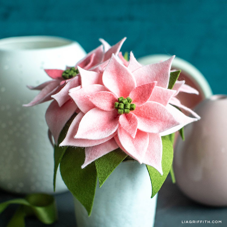 pink felt poinsettia plants in white vase with empty vases in background