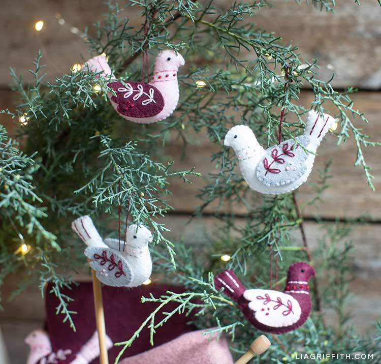 embroidered felt bird ornaments hanging on holiday tree