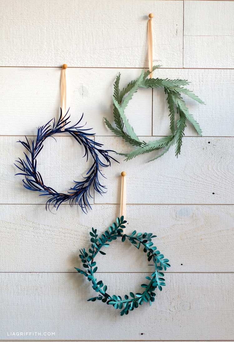 mini evergreen paper wreaths hanging on white wall
