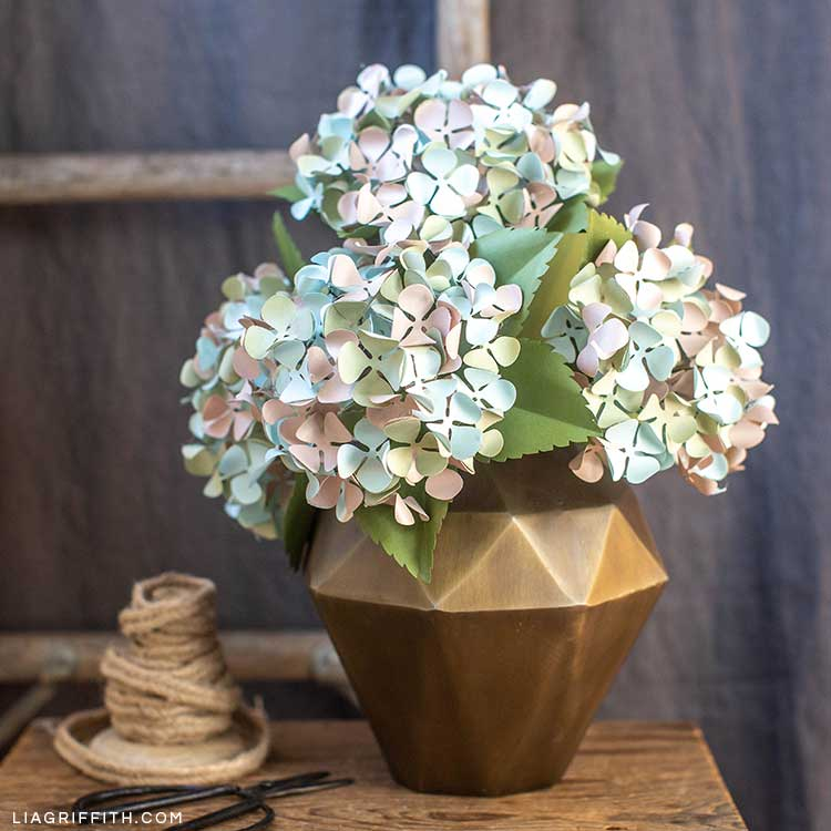 frosted paper hydrangeas in gold geometric vase on table