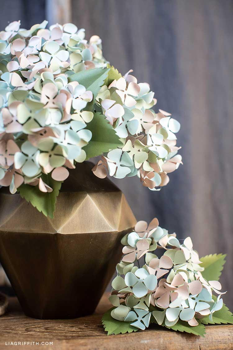 frosted paper hydrangeas in gold vase and loose on table