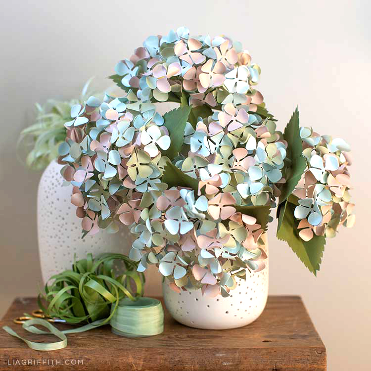 frosted paper hydrangeas in white vase next to paper air plant and green ribbon