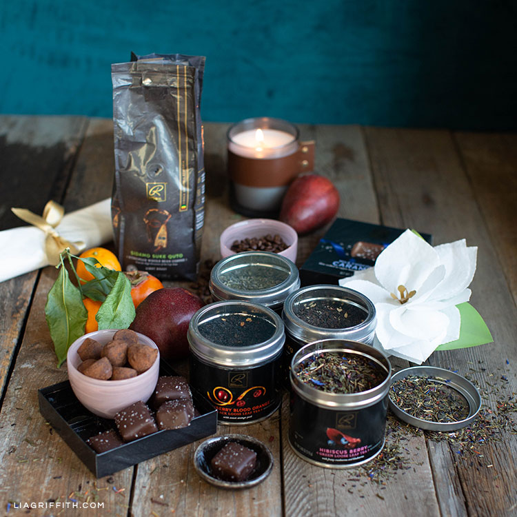 holiday gift basket items including truffles, caramels, loose-leaf tea, coffee, fruit, candle, and white paper poinsettia