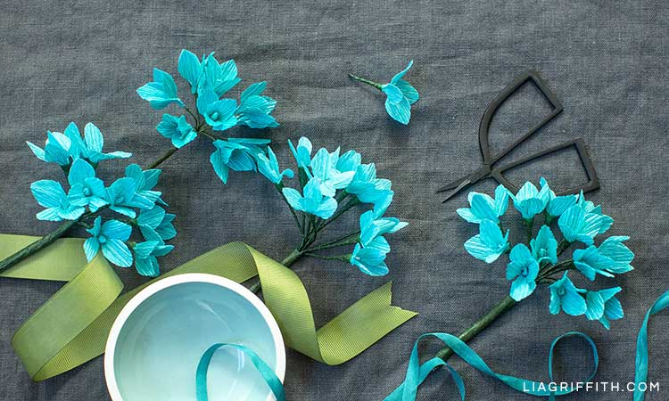teal crepe paper hydrangea flowers on grey sheet with green ribbon, scissors, and white bowl