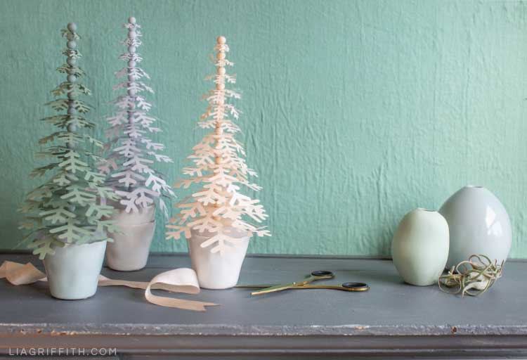 paper snowflake trees in tiny pots on mantel next to ribbon, scissors, and small vases