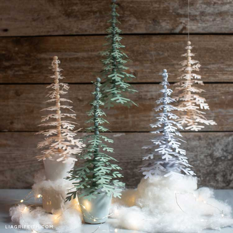 paper snowflake trees in tiny pots on mantel with fake snow and paper trees hanging in the background