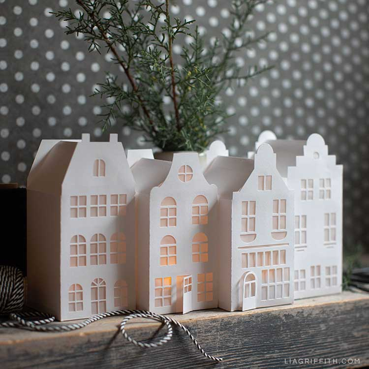 paper canal houses on mantel with fresh greenery against grey and white polka-dot background