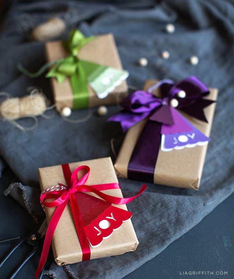 Purple, red, and green Christmas tree gift tags on wrapped presents