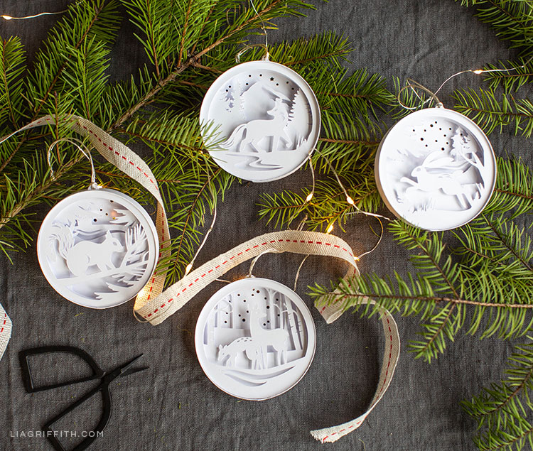 3D paper woodland ornaments on pine tree branches with ribbon and scissors